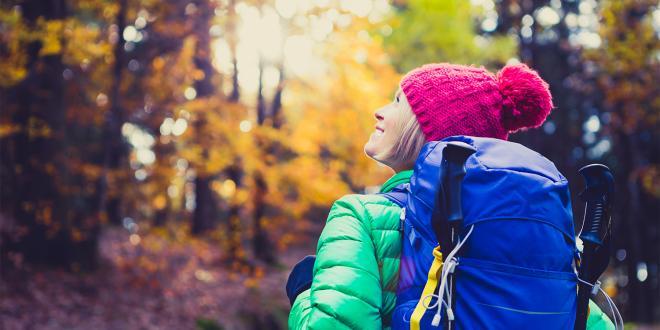 a woman hiking through the fall foliage